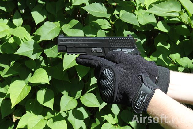 Holding a gun.