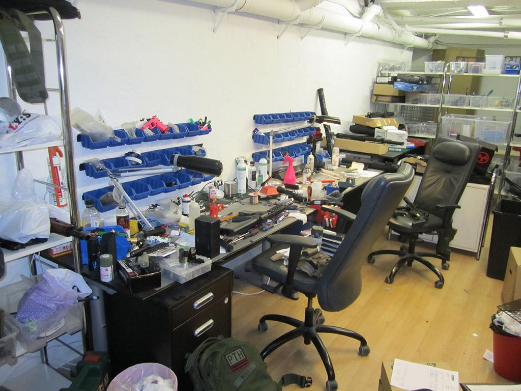 Butikens vapenverkstad där två mekaniker jobbar.
